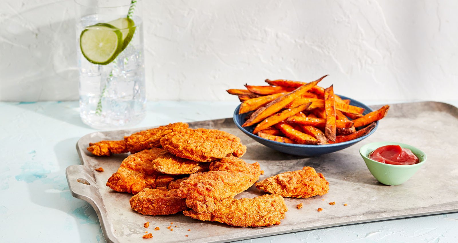 CAULIPOWER Chicken Tenders on a tray with a bowl of sweet potato fries
