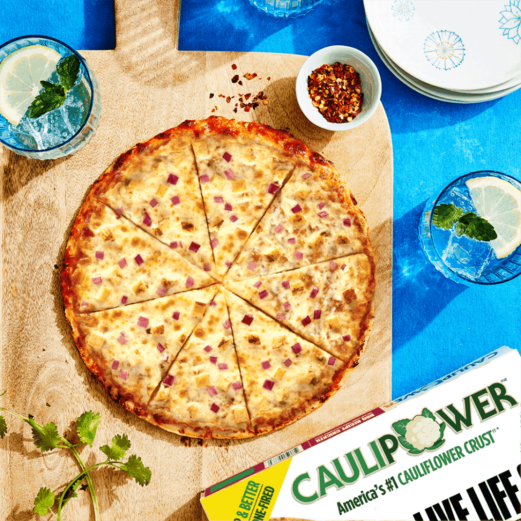 A CAULIPOWER BBQ Style Chicken BIGGER pizza on a wooden cutting board
